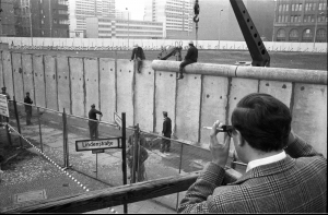 Foto: Ein Besucher einer Aussichtsplattform fotografiert das Anbringen der Rohrauflage auf die Grenzmauer 75 an der Zimmerstraße